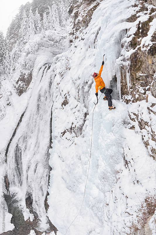 Climber ascending a frozen waterfal  by RG&B Images for Stocksy United