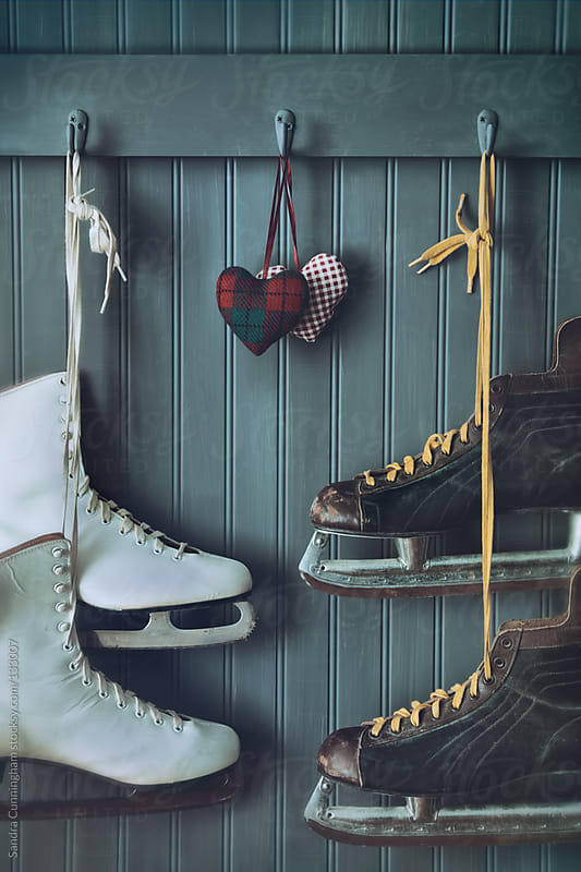 Woman and men skates on coat hooks with hearts by Sandra Cunningham for Stocksy United