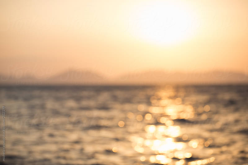 Sun reflecting on the sea at sunset, blurred by michela ravasio for Stocksy United