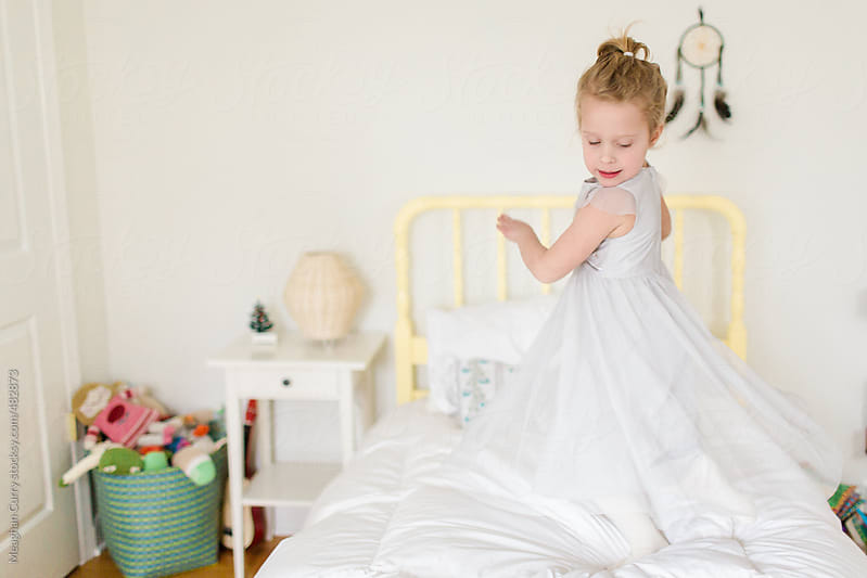 little girl dances and twirls on her bed by Meaghan Curry for Stocksy United