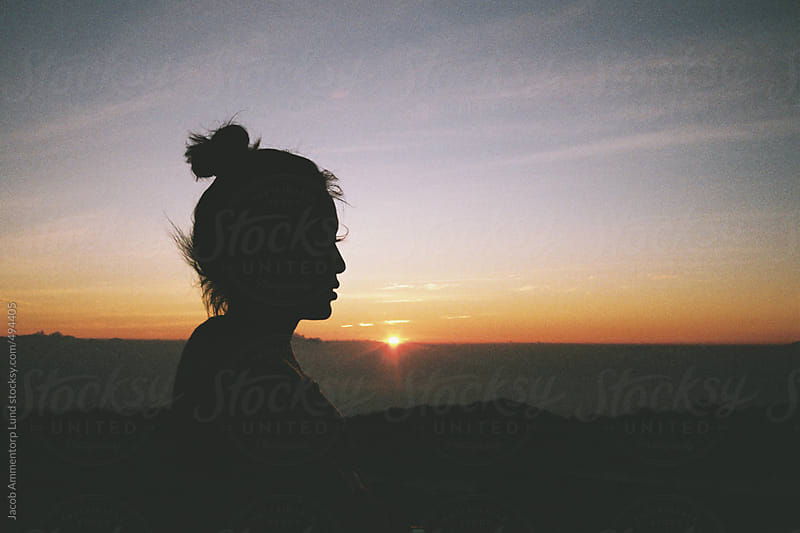 Silhouette of woman in sunset by Jacob Ammentorp Lund for Stocksy United