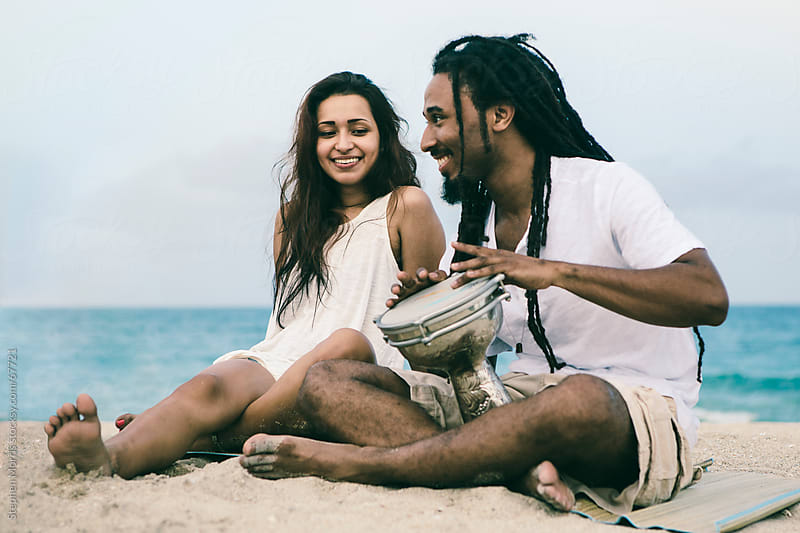 Man Playing drum with Woman on the Beach by Stephen Morris for Stocksy United