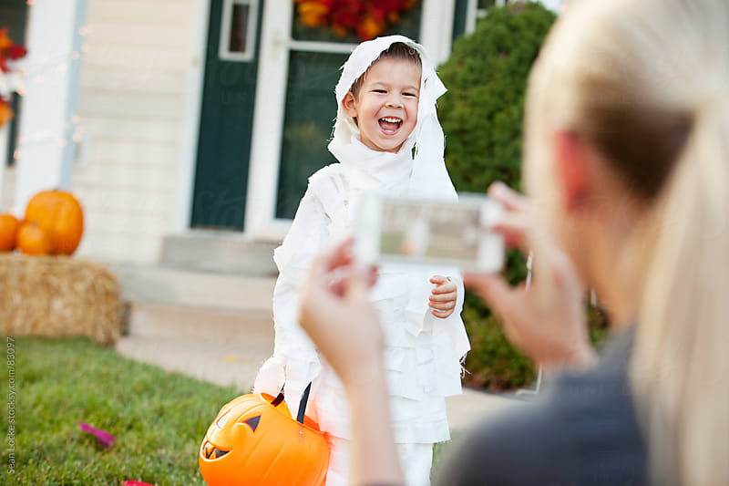 Halloween: Boy Laughs As Mother Snaps Photo by Sean Locke for Stocksy United
