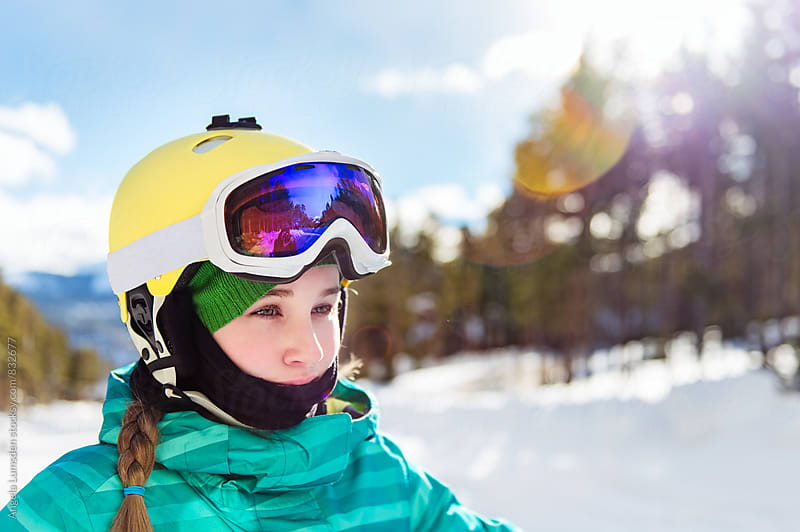 Teenage girl with ski helmet and goggles surveys the slopes in early morning sunshine by Angela Lumsden for Stocksy United