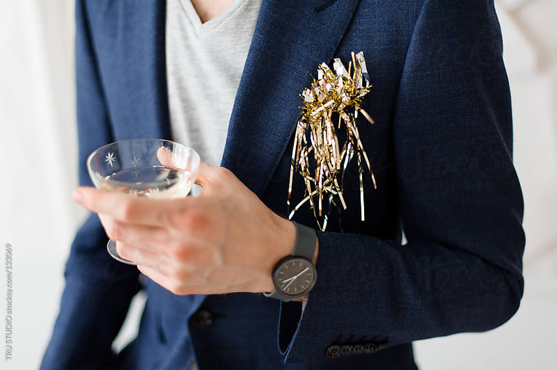 Young man in navy suit holding champagne glass at a party with tinsel on white background. by TRU STUDIO for Stocksy United