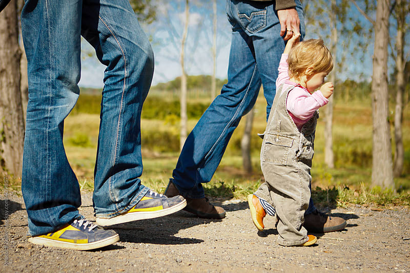 a child walks holding her dad's hand by Rebecca Zeller for Stocksy United