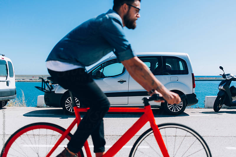 Man riding a bicicle by Leandro Crespi for Stocksy United