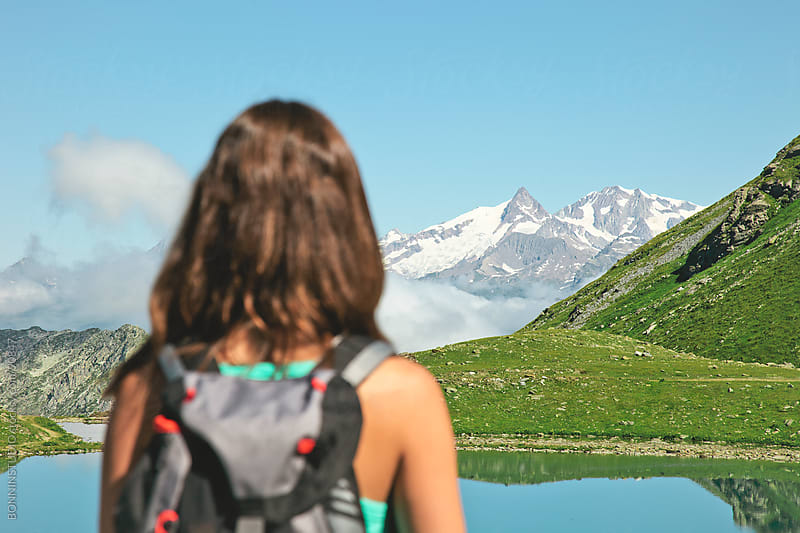 Hiker woman contempling a beautiful lake landscape. Alps, france. by BONNINSTUDIO for Stocksy United
