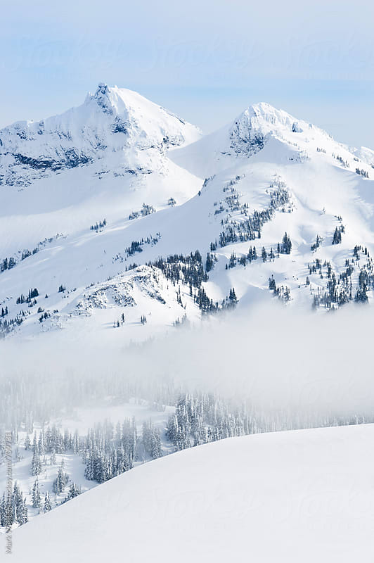Snow-covered mountains in winter by Mark Windom for Stocksy United