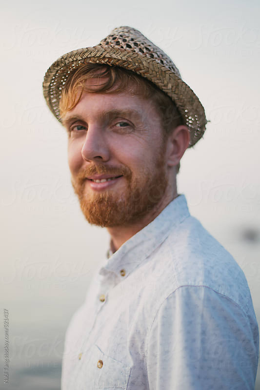 Handsome ginger man portrait with straw hat by the sea by Nabi Tang for Stocksy United