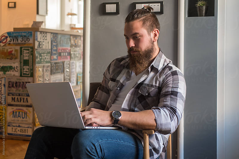 Young Bearded Man Sitting in a Hostel and Using Laptop by Aleksandra Jankovic for Stocksy United