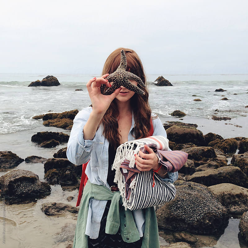 Woman Holding Sea Star in Front of Face by Kevin Russ for Stocksy United