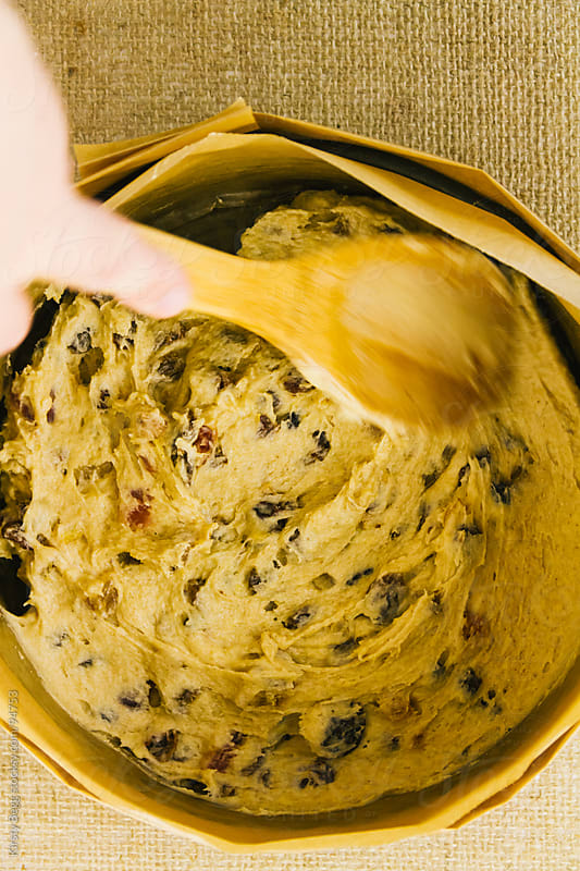 Smoothing fruit cake batter into round pan with wooden spoon by Kirsty Begg for Stocksy United