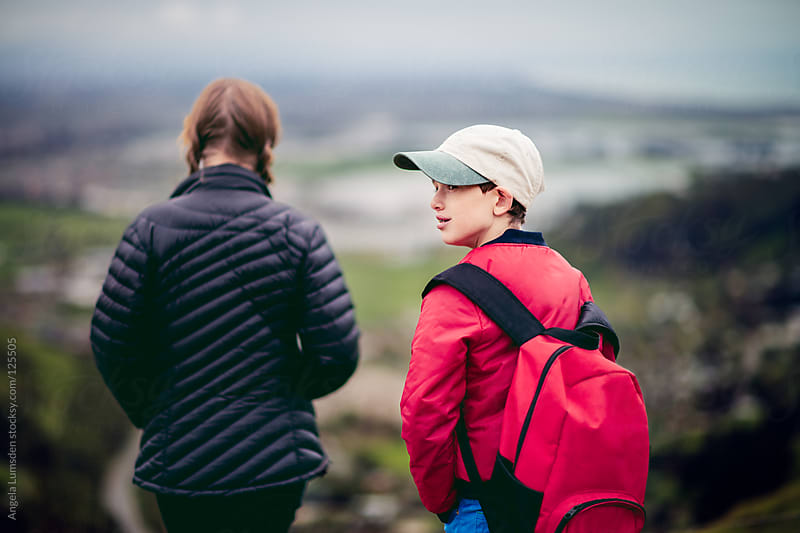 Boy looks back over his shoulder during a hike by Angela Lumsden for Stocksy United