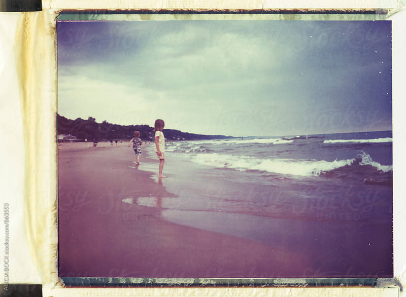 Polaroid Photograph Of Two Children On A Stormy Beach Watching Waves  by ALICIA BOCK for Stocksy United