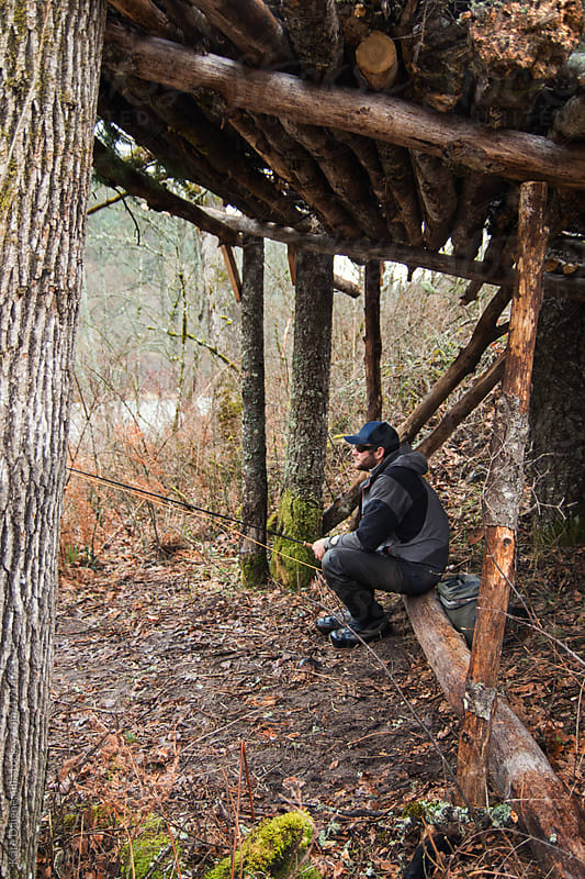 Fly fisherman waits out a downpour in a hand made shelter by the river. by Kate Daigneault for Stocksy United