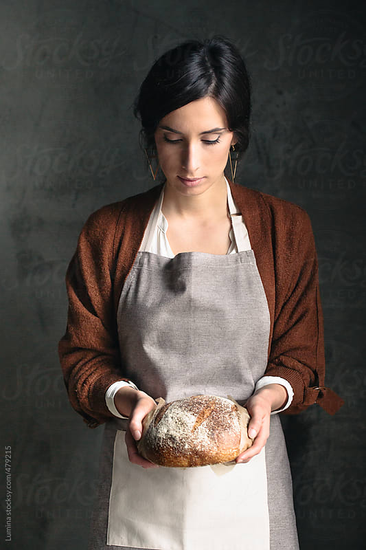 Woman in an Apron Holding Bread by Lumina for Stocksy United