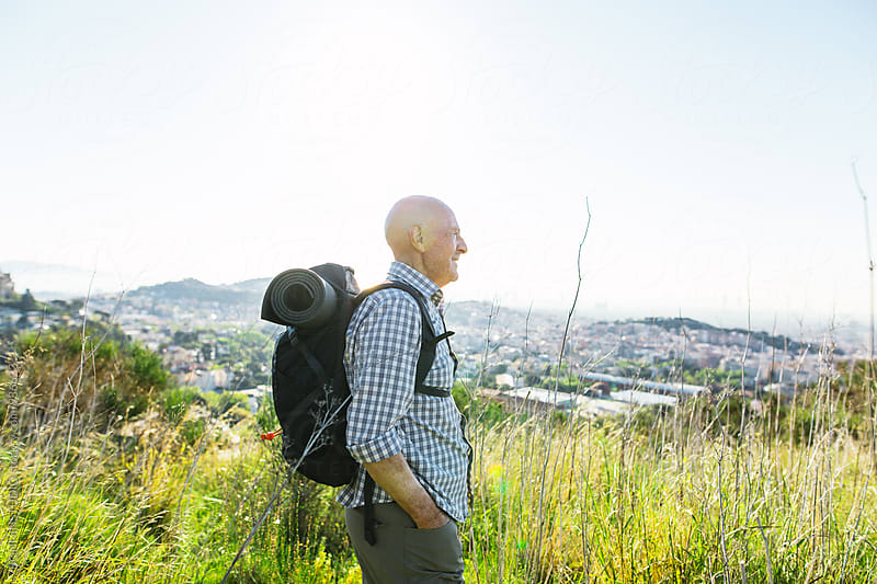 Hiker senior man standing in the mountain over the city. by BONNINSTUDIO for Stocksy United