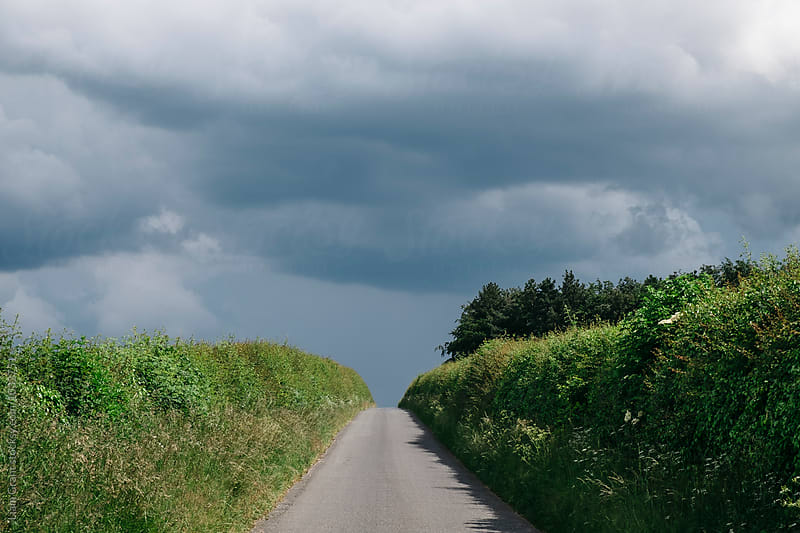 Small country road with storm clouds above. Norfolk, UK. by Liam Grant for Stocksy United