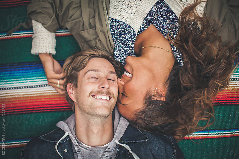 Young couple laying on colorful blanket and smiling. by RZ CREATIVE for Stocksy United