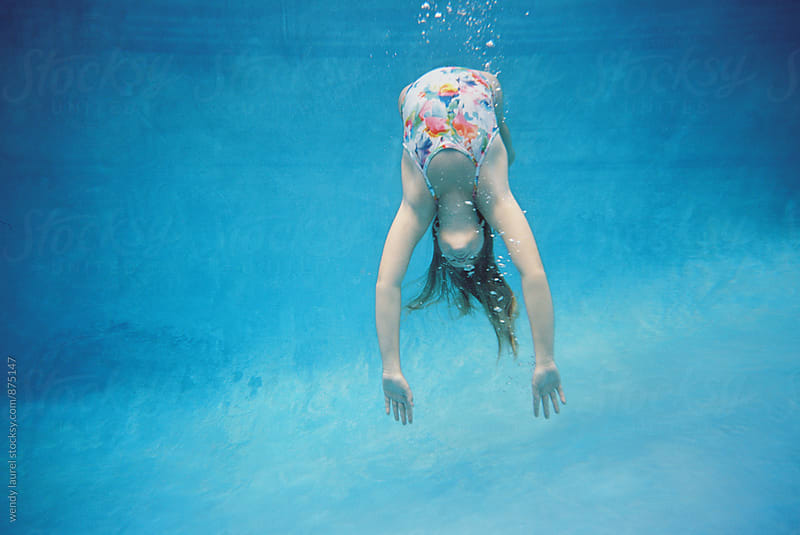 girl doing backbend underwater in deep blue water by wendy laurel for Stocksy United