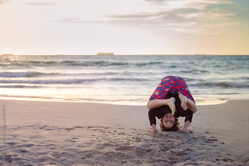 Boy balancing on his head and arms on the beach by Angela Lumsden for Stocksy United