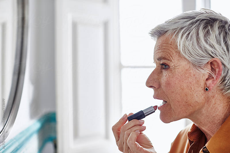 Senior Woman Applying Lipstick At Home by ALTO IMAGES for Stocksy United