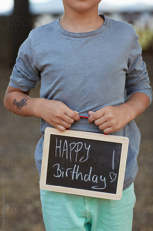 Child holding a black board with the word happy birthday by Miquel Llonch for Stocksy United
