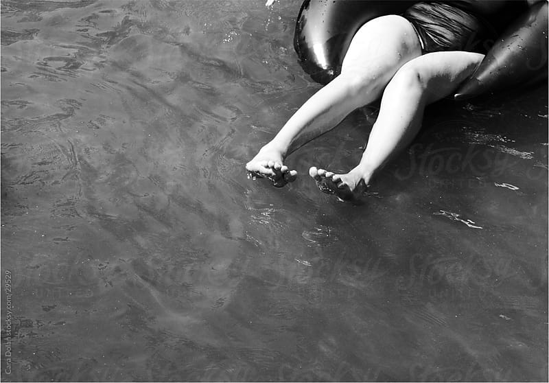 Woman floating in an innertube on a lake by Cara Slifka for Stocksy United