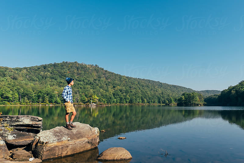 Portrait of teen boy looking at lake by kelli kim for Stocksy United