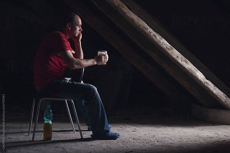 Man Sitting in Attic Alone Drinking Beer by Geoffrey Hammond for Stocksy United