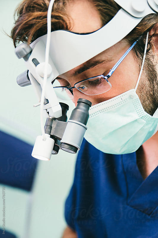 Dentist at work with magnifying glasses by Inuk Studio for Stocksy United