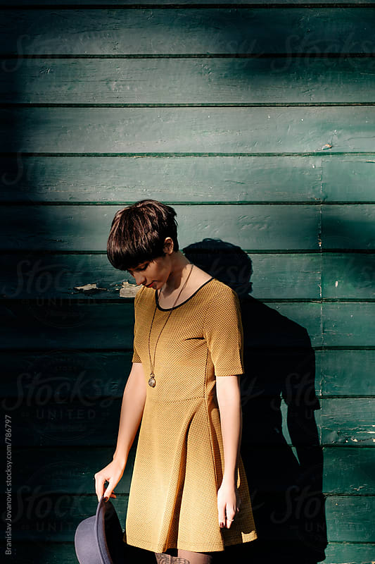 Woman in Yellow Dress Looking Down by Brkati Krokodil for Stocksy United