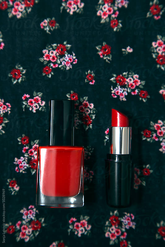 red lipstick and nail polish on black background by Sonja Lekovic for Stocksy United