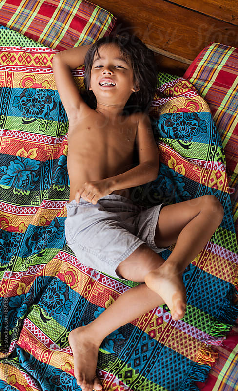 Cute little boy playing on colorful mattress. by Marko Milanovic for Stocksy United