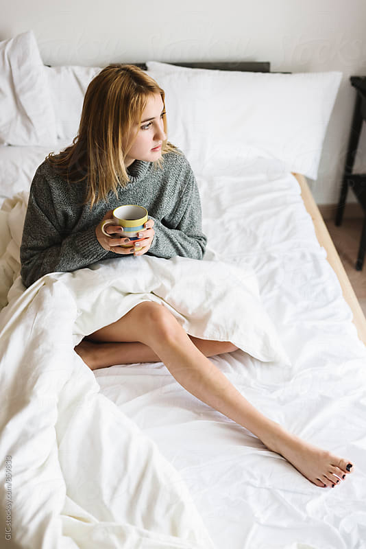 Woman holding a coffee mug in the bed by Simone Becchetti for Stocksy United