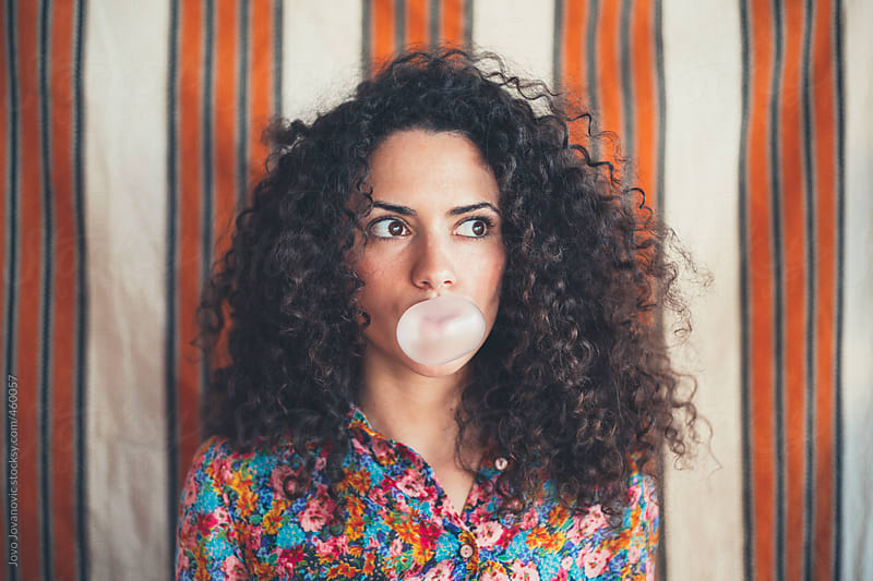 Girl with curly hair blowing a bubble with a pink bubble gum by Jovo Jovanovic for Stocksy United