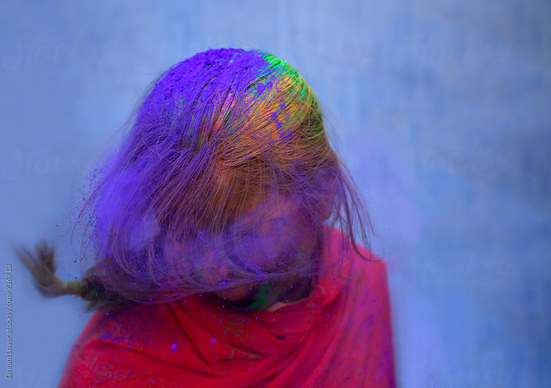 Young woman shaking head and spreading colored powder by PARTHA PAL for Stocksy United