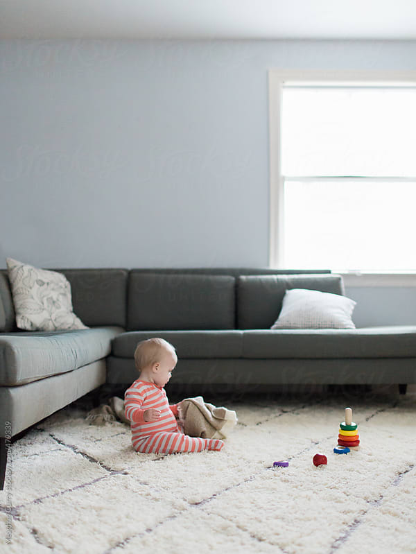 baby playing with a wooden toy in a living room by Meaghan Curry for Stocksy United