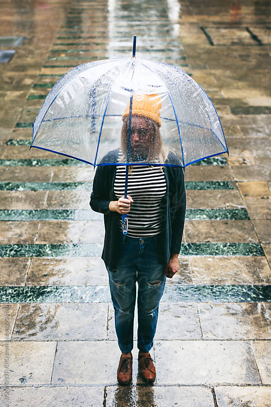 Woman holding an umbrella in a rainy day. by BONNINSTUDIO for Stocksy United