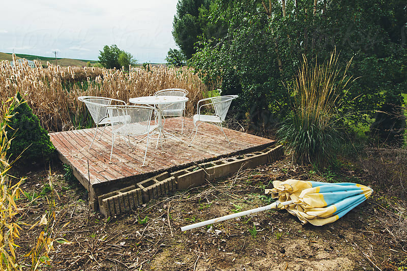 Neglected Table, Chairs, and Umbrella by Luke Mattson for Stocksy United