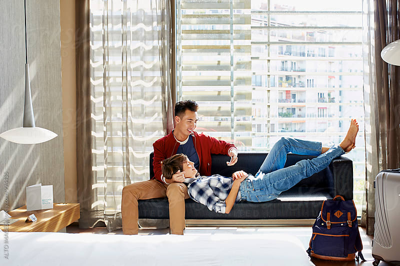 Happy Loving Couple Relaxing On Sofa In Hotel Room by ALTO IMAGES for Stocksy United