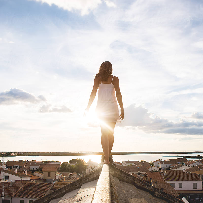 Woman standing in balance on a rooftop in the sunlight  by RG&B Images for Stocksy United