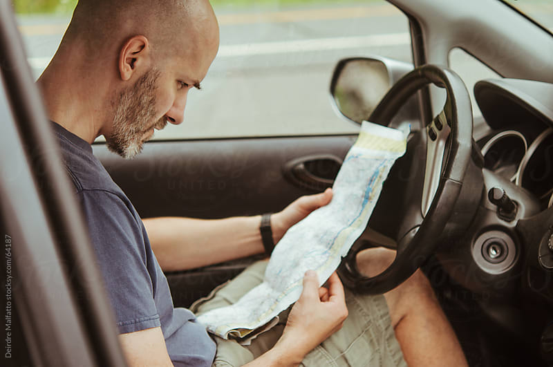 Man reading a worn map in a car by Deirdre Malfatto for Stocksy United