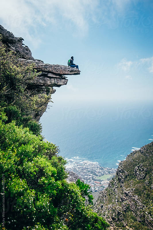 Hiker on an exposed mountain ledge overlooking the sea by Micky Wiswedel for Stocksy United