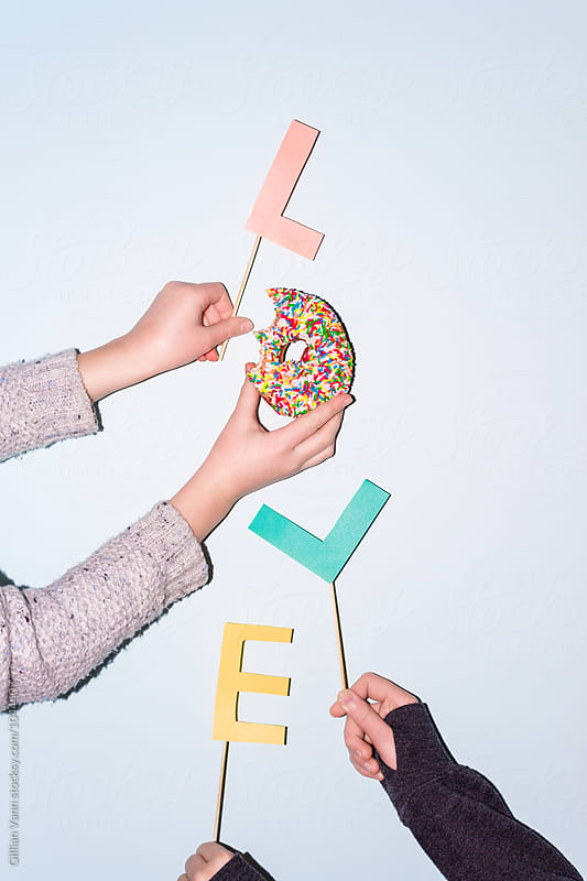 the word love spelled with a donut by Gillian Vann for Stocksy United