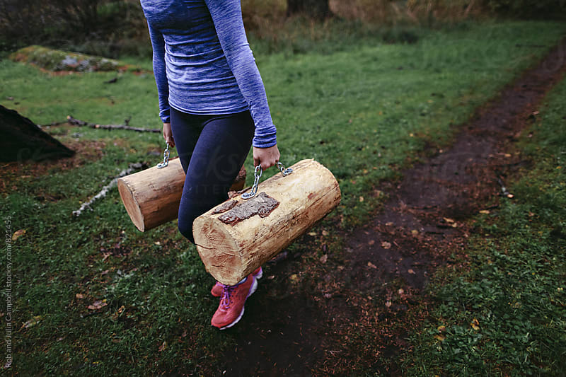 Woman walking with heavy logs at rainy outdoor bootcamp by Rob and Julia Campbell for Stocksy United