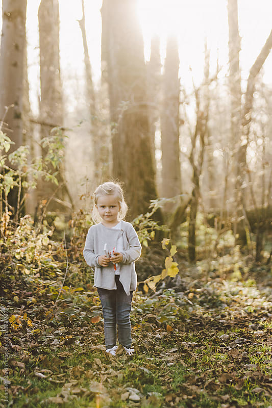 fairytale looking cute little girl standing in autumal forest with sweets in her hands by Leander Nardin for Stocksy United