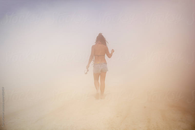 A girl walking in a dust storm in the desert by Gary Parker for Stocksy United