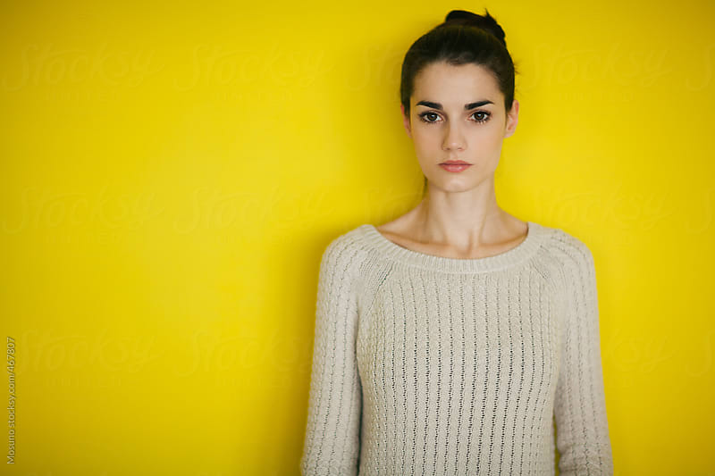 Portrait of a Woman in Sweater Standing Against Yellow Wall  by Mosuno for Stocksy United